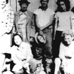 This photograph was taken in 1942 at a relocation camp in Parlier, California where the Yamamotos were obliged to live during World War II. To the left is Mrs. Ramona Brown, and to the right Mrs. Marzieh Gail, both renowned Bahá'í writers. Mr. Kanichi Yamamoto is standing with his son Goro, and daughter Fumiko is kneeling. Kneeling on the right is Mrs. Margaret Cavanaugh, sister of the compiler.